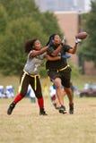 女性旗标橄榄球收货人抓住通过 免版税库存图片