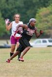 女性旗标橄榄球球员为端线区冲刺 库存图片