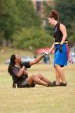 女性旗标橄榄球球员帮助队友起来 图库摄影