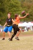 女性旗标橄榄球球员捉住通过 免版税库存照片