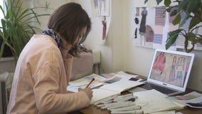 女性时装设计师画象,在她明亮的演播室画草稿 股票录像