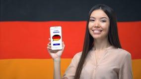 女性显示的手机与学会德国应用程序,在背景,教育的旗子 股票录像