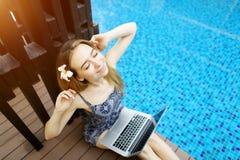 女性晴朗的画象在水池背景的坚苦工作以后舒展手和膝上型计算机键盘  图库摄影