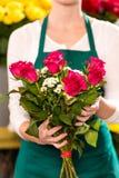 女性暂挂的花束开花玫瑰花店 库存图片