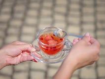 女性有一个杯子的` s手莓果液体在石头弄脏了背景 可口和自然草莓茶 免版税库存图片