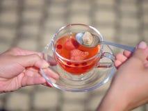 女性有一个杯子的` s手莓果液体在石头弄脏了背景 可口和自然草莓茶 免版税库存照片
