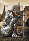 女性有一座城堡的战士骑士下跪佩带的装饰金属装甲在背景中 皇族释放例证