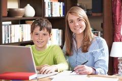 女性有家庭作业的家庭教师帮助的男孩 库存图片
