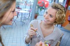 女性朋友吃午餐一起在购物中心餐馆 库存照片
