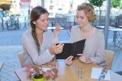 女性朋友吃午餐一起在购物中心餐馆 免版税库存图片