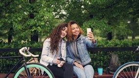 女性朋友在拿着咖啡的公园采取与智能手机的selfie坐长凳,少妇摆在与 股票录像