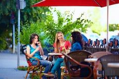 年轻女性朋友坐咖啡馆大阳台,户外 库存图片