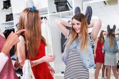 年轻女性朋友获得乐趣,当购物在服装店时 使用她的鞋子的俏丽的女孩显示滑稽的兔宝宝耳朵 库存图片