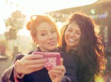 女性朋友采取selfie的两名妇女获得乐趣在周末逃走期间 库存图片