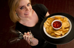 女性服务器带来开胃菜芯片辣调味汁食物 库存图片