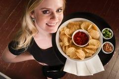 女性服务器带来开胃菜芯片辣调味汁食物 库存照片