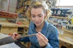 女性木匠在车间工作 免版税库存图片