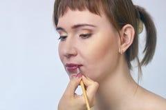 女性构成模型和visagiste手有-被集中的唇膏刷子的 库存照片