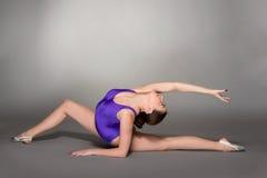 年轻女性柔术表演者在紫色紧身连衣裤摆在,在黑暗的背景 免版税库存图片