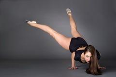 年轻女性柔术表演者,平衡在她的在黑暗的背景的手棕榈  免版税图库摄影