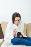 女性模型得了用白色毯子在家报道的寒冷 免版税库存图片