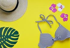 女性比基尼泳装泳装和草帽,夏时顶视图舱内甲板放置黄色背景拷贝空间横幅概念,热带叶子flo 免版税库存照片