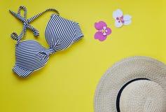 女性比基尼泳装泳装和草帽,夏时顶视图舱内甲板放置黄色背景拷贝空间横幅概念,热带叶子flo 库存照片