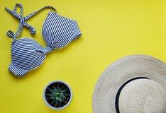 女性比基尼泳装泳装和草帽,夏时顶视图舱内甲板放置黄色背景拷贝空间横幅概念,热带叶子flo 免版税库存图片