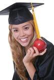 女性毕业生用苹果 免版税图库摄影