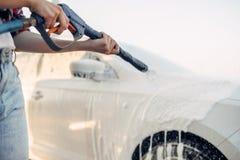 女性洗涤从汽车的泡沫 免版税库存图片