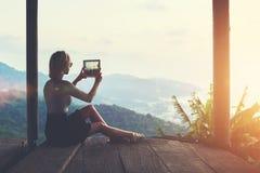 女性流浪汉做与一个惊人的密林风景的数字式片剂照相机的照片 免版税库存照片