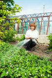 女性浇灌的庭院床 库存照片