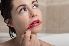 女性消沉 一名妇女在有石化神色的卫生间大幅度削减在她的面孔的唇膏 库存照片