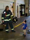 女性消防队员和小男孩 免版税库存照片