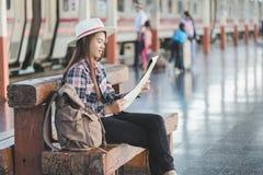 女性游人为夏天旅行看见地图在火车站,旅行和休息在假日期间的 免版税库存图片
