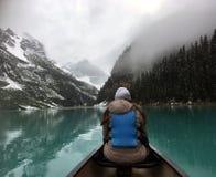 女性游人享受从一艘皮船的看法在路易丝湖 库存图片