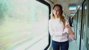 年轻女性游人喜欢旅行和旅行,显示姿态并且在火车的大窗口附近站立 影视素材