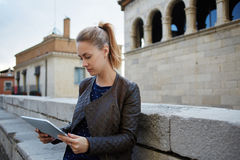 女性游人在互联网搜寻通过关于城市的历史的数字式片剂信息 库存照片