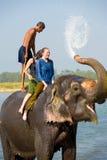 女性游人大象乘驾树干水飞溅 库存图片