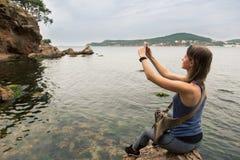女性游人拍与手机的照片 免版税库存图片