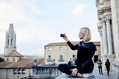 女性游人拍摄城市视图录影在手机的 图库摄影