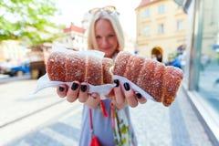年轻女性游人用传统捷克点心叫trdelnik 布拉格 免版税库存照片