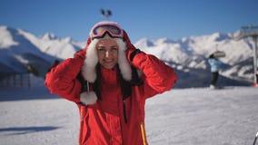 女性滑雪者特写镜头画象山滑雪场的 看照相机的滑雪服和滑雪风镜的愉快的妇女和 股票视频