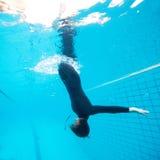 女性潜水向下在游泳池 免版税库存图片