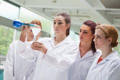 女性烧瓶液体倾吐的科学学员 免版税库存图片