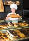 女性烹调展示和卖对顾客酥皮点心 图库摄影