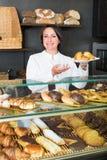 女性烹调展示和卖对顾客酥皮点心 免版税库存照片