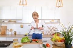 女性烹饪博客作者在手上拿着电话并且组成混合涂料 免版税库存照片