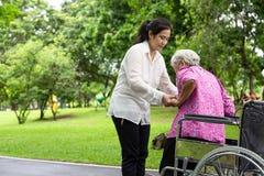 女性照料者亚洲或年轻护士支持,站起来的帮助的资深妇女从轮椅在室外公园,耐心母亲与 库存照片