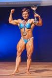 女性爱好健美者庆祝她的在阶段的冠军胜利 免版税库存照片
